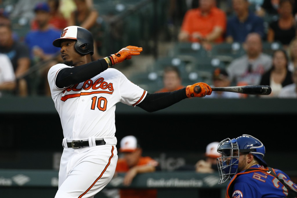 Baltimore Orioles' Adam Jones follows through on an RBI single in front of New York Mets catcher Kevin Plawecki during the first inning of a baseball ...