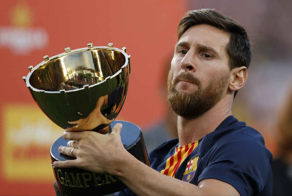 FC Barcelona's Lionel Messi holds up the Joan Gamper trophy after a friendly soccer match between FC Barcelona and Boca Juniors at the Camp Nou stadiu...