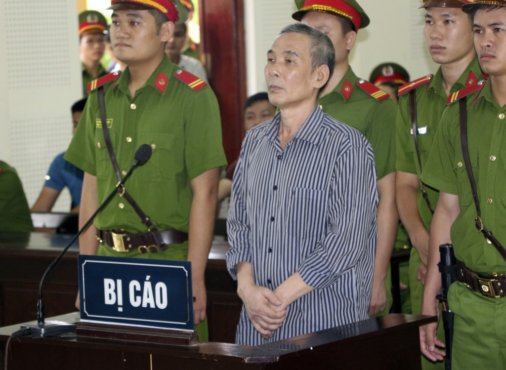 Activist Le Dinh Luong, center, stands trial in central province of Nghe An, Vietnam, Thursday, Aug. 16, 2018. Luong was sentenced to 20 years in pris...
