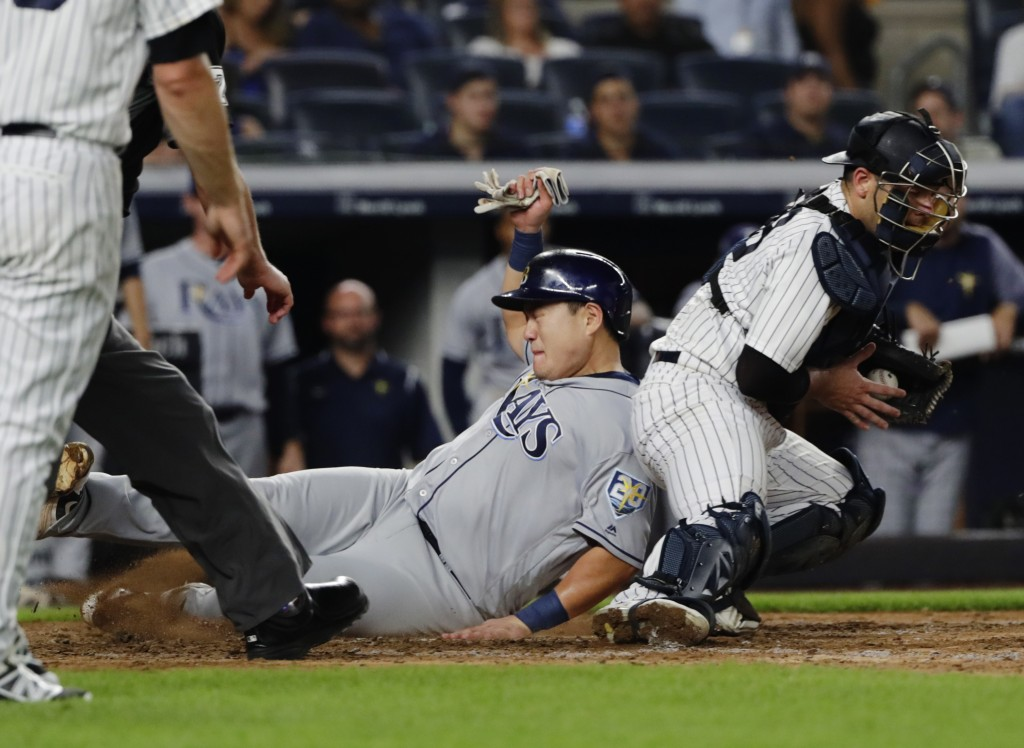 Tampa Bay Rays' Ji-Man Choi, center, slides past New York Yankees catcher Austin Romine to score on a single by Brandon Lowe during the fifth inning o...