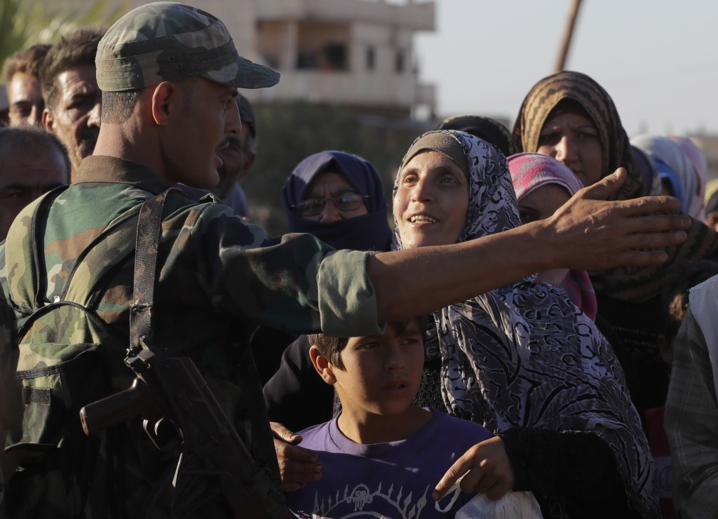 A woman talks with a soldier of the Syrian army during distribution of humanitarian aid from the Russian military in the town of Rastan, Syria, Wednes...