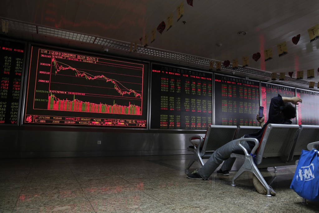 A man browses his smartphone in front of an electronic board displaying stock prices at a brokerage house in Beijing, Thursday, Aug. 16, 2018. Asian s...