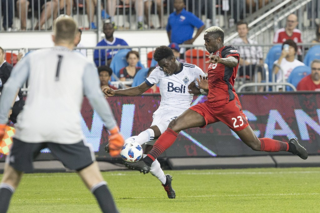 Vancouver Whitecaps' Alphonso Davies, center, tries to cross the ball past Toronto FC's Chris Mavinga during the first half in the second leg of the C...