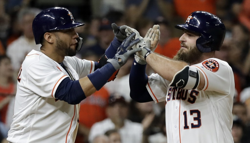 Houston Astros' Tyler White (13) celebrates with Yuli Gurriel after both scored on White's home run against the Colorado Rockies during the fifth inni...