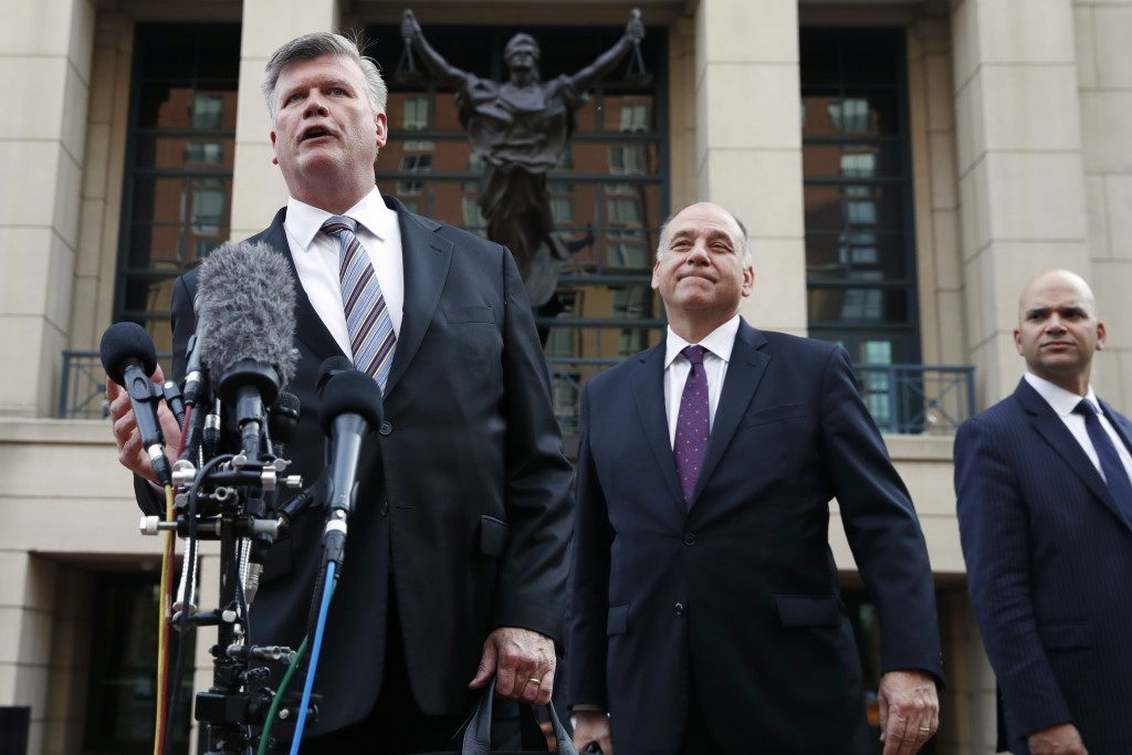 Defense attorney Kevin Downing, left, with Thomas Zehnle and Jay Nanavati, right, makes a statement to the media outside federal court after closing a...