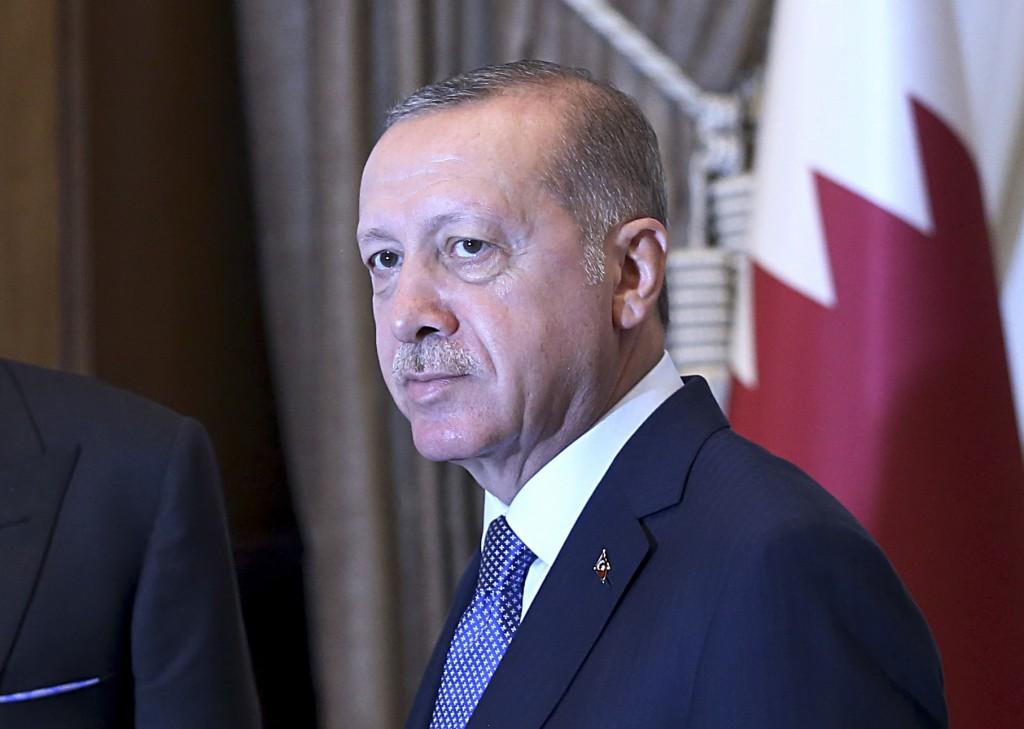 Turkey's President Recep Tayyip Erdogan, as he shakes hands with Qatar's Emir Sheikh Tamim bin Hamad Al Thani prior to their talks at the Presidential...