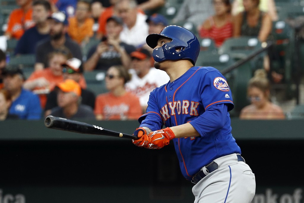 New York Mets' Wilmer Flores watches an RBI sacrifice fly during the first inning against the Baltimore Orioles in a baseball game Wednesday, Aug. 15,...