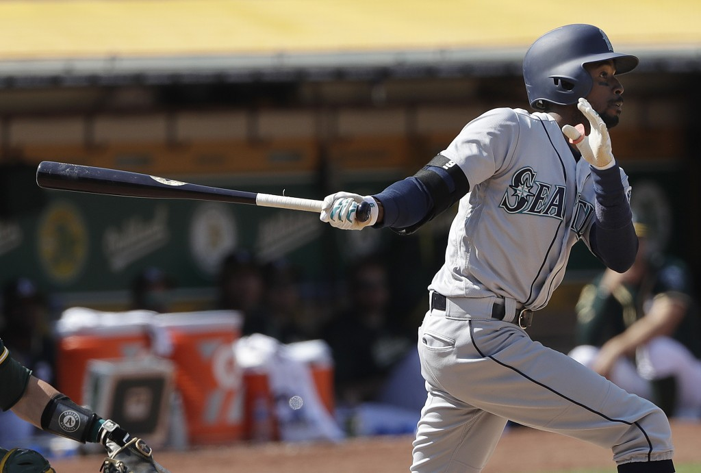 Seattle Mariners' Dee Gordon watches a two-run home run against the Oakland Athletics during the 12th inning of a baseball game in Oakland, Calif., We...