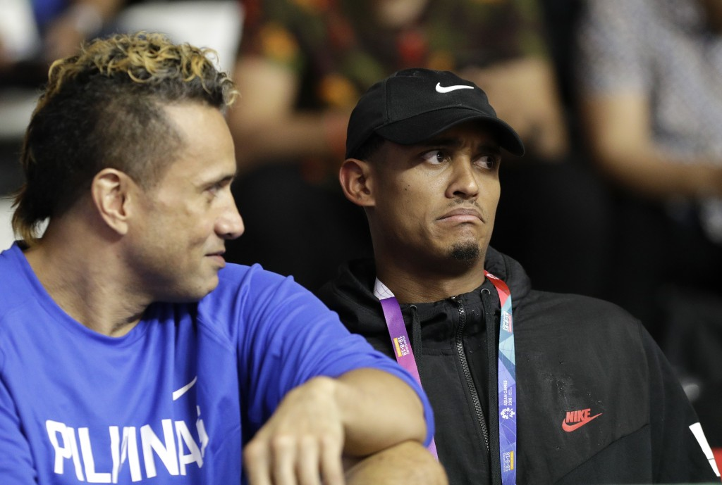 Filipino-American NBA player Jordan Clarkson, right, watches with Philippines' Pauliasi Taulava on the bench as he arrives during a match against Phil...