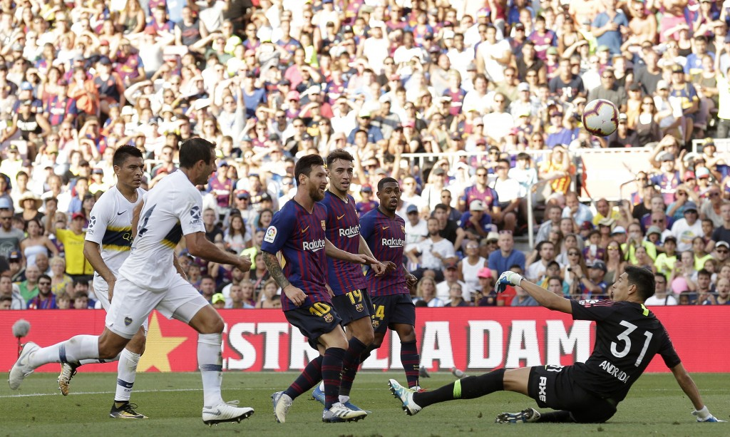 FC Barcelona's Lionel Messi, center, scores during the Joan Gamper trophy friendly soccer match between FC Barcelona and Boca Juniors at the Camp Nou ...