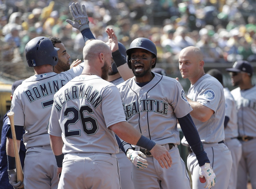 Seattle Mariners' Dee Gordon, center right, is congratulated by teammates after hitting a two-run home run against the Oakland Athletics during the 12...