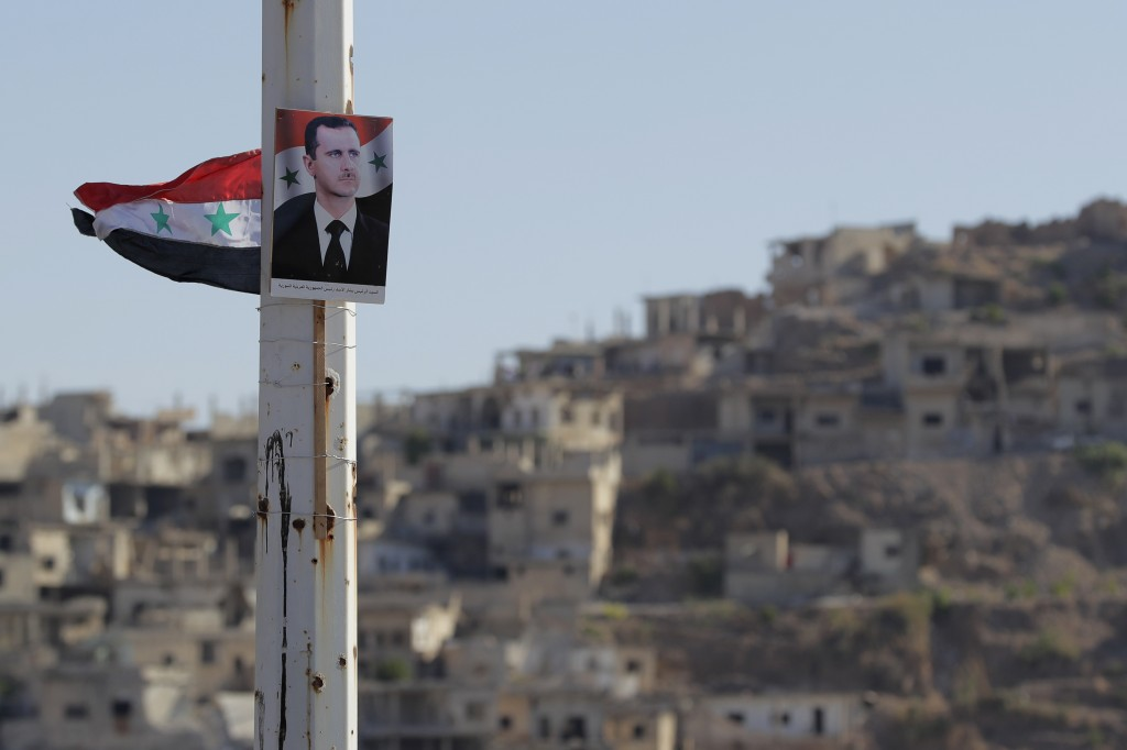 A portrait of Syrian President Bashar Assad is fastened on the pillar in the town of Rastan, Syria, Wednesday, Aug. 15, 2018. The Russian Defense Mini...