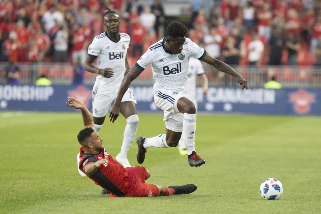 Vancouver Whitecaps forward Alphonso Davies, right, leaps over the challenge by Toronto FC defender Justin Morrow during the first half in the second ...