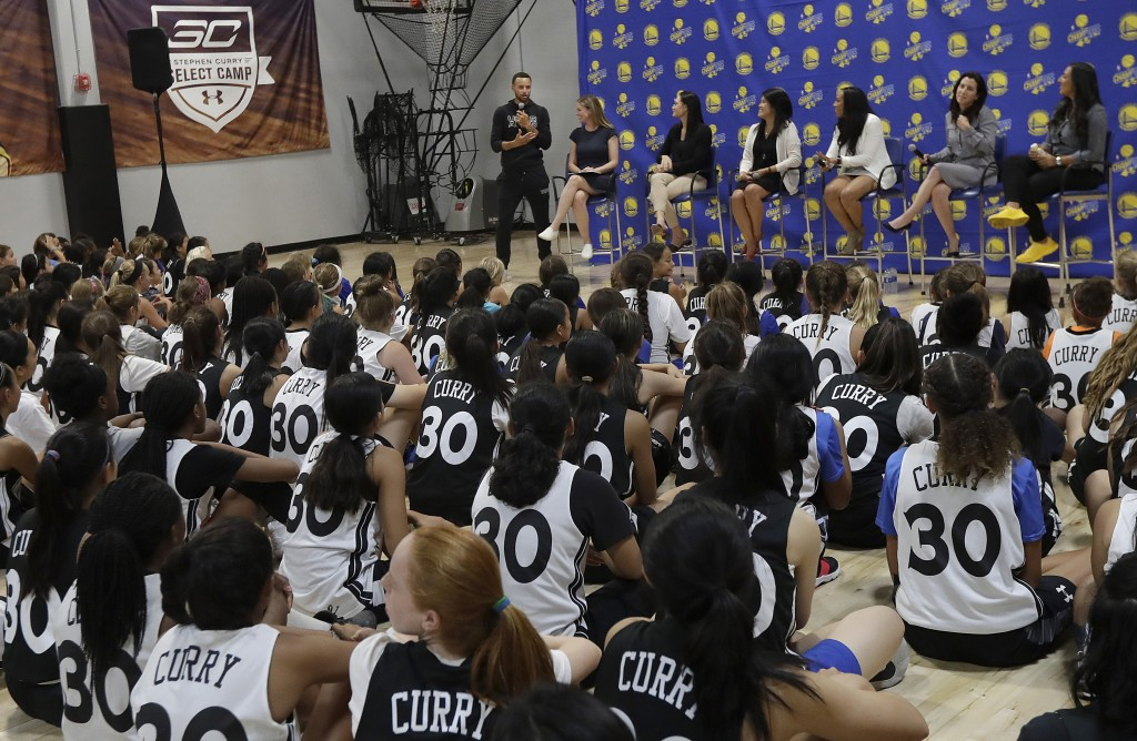 Golden State Warriors' Stephen Curry, top center, speaks to basketball camp participants while hosting a panel for women in sports at Ultimate Fieldho...