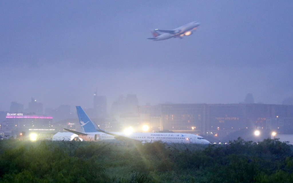 A Philippine Airlines passenger plane takes off while a Boeing passenger plane from China, a Xiamen Air, lies on the grassy portion of the runway of t...