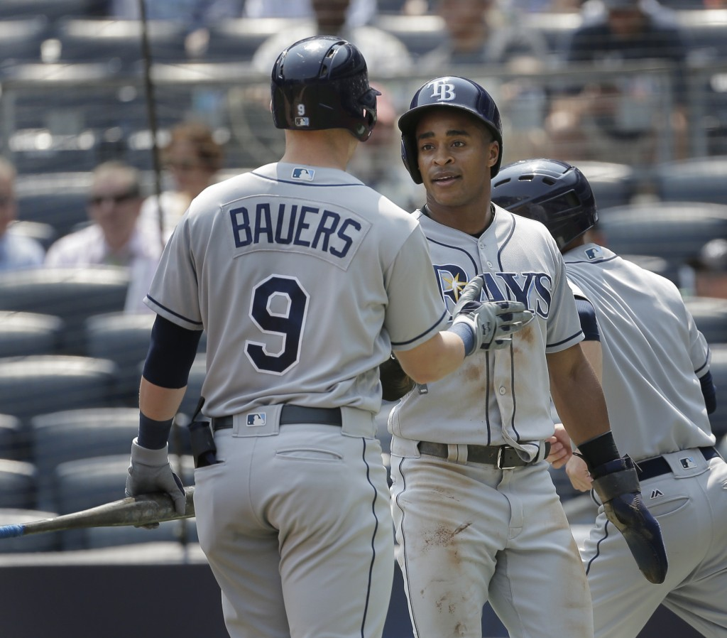 Tampa Bay Rays' Mallex Smith, right, is greeted by Jake Bauers (9) after scoring a run during the first inning of a baseball game against the New York...