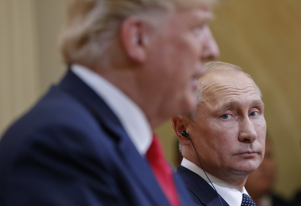 FILE - In this July 16, 2018 file photo Russian President Vladimir Putin, right, looks over towards U.S. President Donald Trump, left, as Trump speaks...