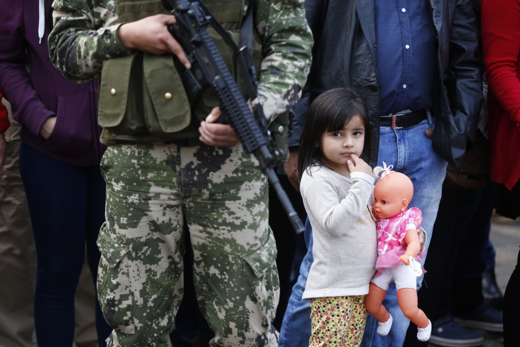 In this Aug. 15, 2018 photo, a girl holding her doll watches a military parade marking the 481th anniversary of the founding of Asuncion, Paraguay. Pa...