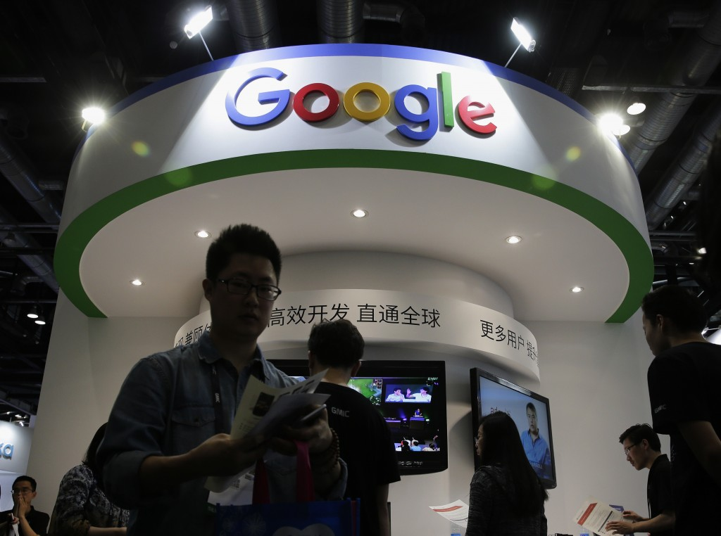 FILE - In this April 28, 2016, file photo, visitors gather at a display booth for Google at the 2016 Global Mobile Internet Conference (GMIC) in Beiji