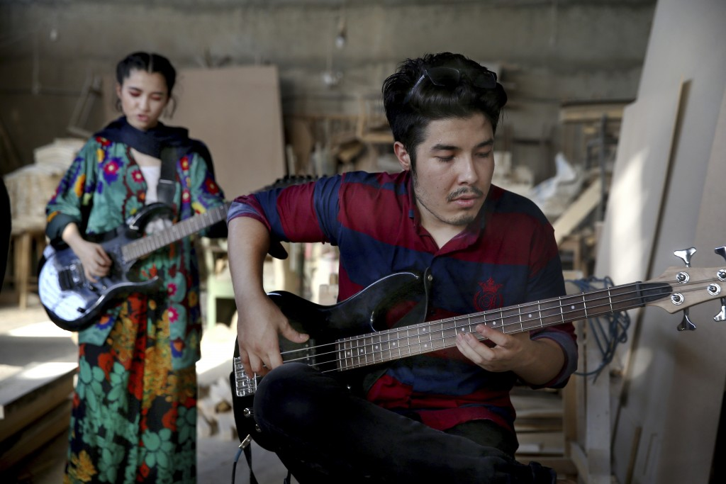In this July 26, 2018 photo, Afghan musicians Mohammad Rezai, right, and Soraya Hosseini, members of the Arikayn rock band, play guitar at a furniture...