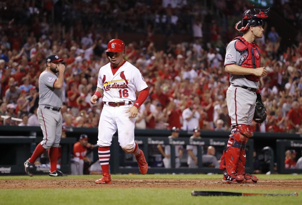 St. Louis Cardinals' Kolten Wong (16) scores between starting pitcher Tanner Roark, left, and catcher Matt Wieters during the sixth inning of a baseba...