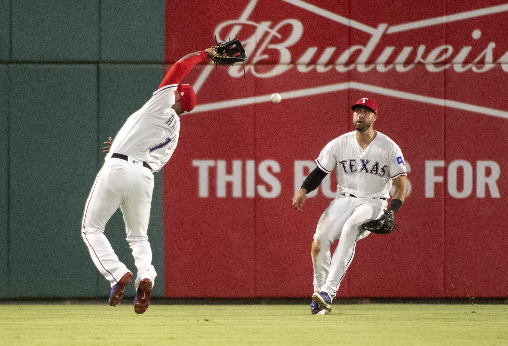 Texas Rangers shortstop Elvis Andrus (1) can't make the catch on a pop fly by Los Angeles Angels' Andrelton Simmons as left fielder Joey Gallo backs u...