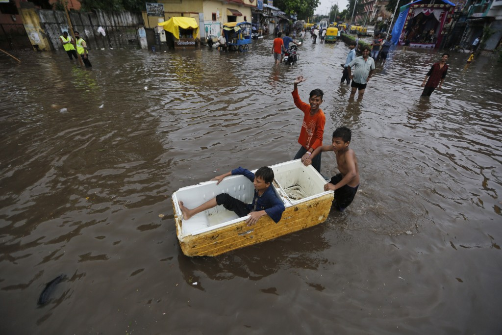 Indian children play in floodwaters after heavy rainfall in Ahmadabad, India, Friday, Aug. 17, 2018. India receives its annual rainfall from June-Octo...