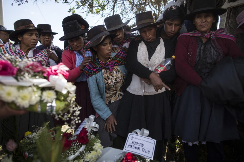 In this Aug. 15, 2018 photo, the relatives of people killed by Shining Path guerrillas and the Peruvian army in the 1980s look at the remains of their...