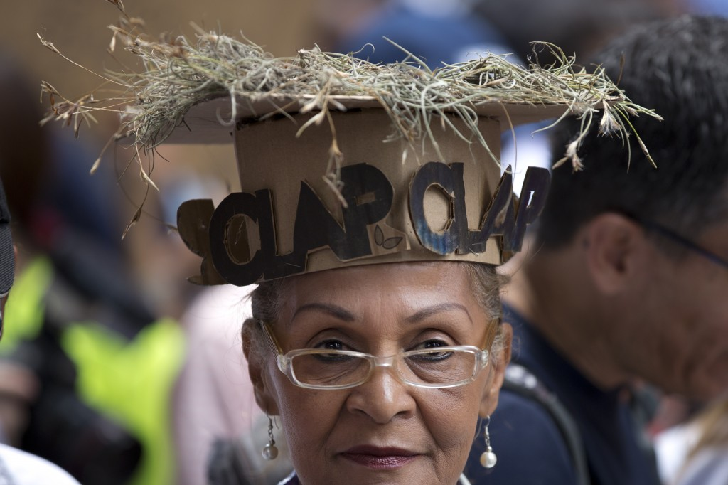 """A woman wears a cardboard hat with dry grass on top and letters in Spanish that read """"CLAP"""", meaning the boxes with food provided by the government ru..."""