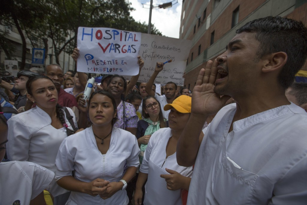 Nurses shout anti-government slogans outside a hospital during a protests against the government of President Nicolas Maduro, in Caracas, Venezuela, T...