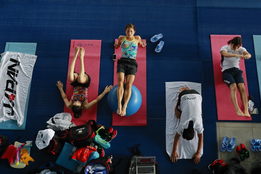 Members of Japan's swimming team stretch during at training session at the 18th Asian Games in Jakarta, Indonesia, Friday, Aug. 17, 2018. (AP Photo/Be...
