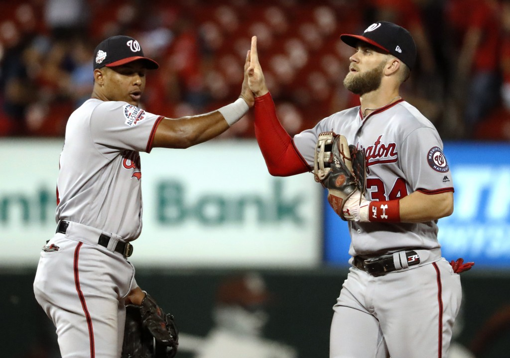 Washington Nationals' Bryce Harper, right, and Wilmer Difo celebrate following the team's 5-4 victory over the St. Louis Cardinals in a baseball game ...