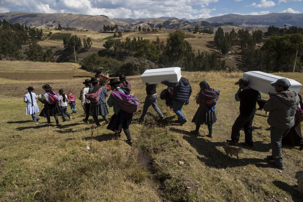 In this Aug. 15, 2018 photo, villagers carry the remains of people killed by the Shining Path guerrillas in 1984, during their proper burial in Tantan...