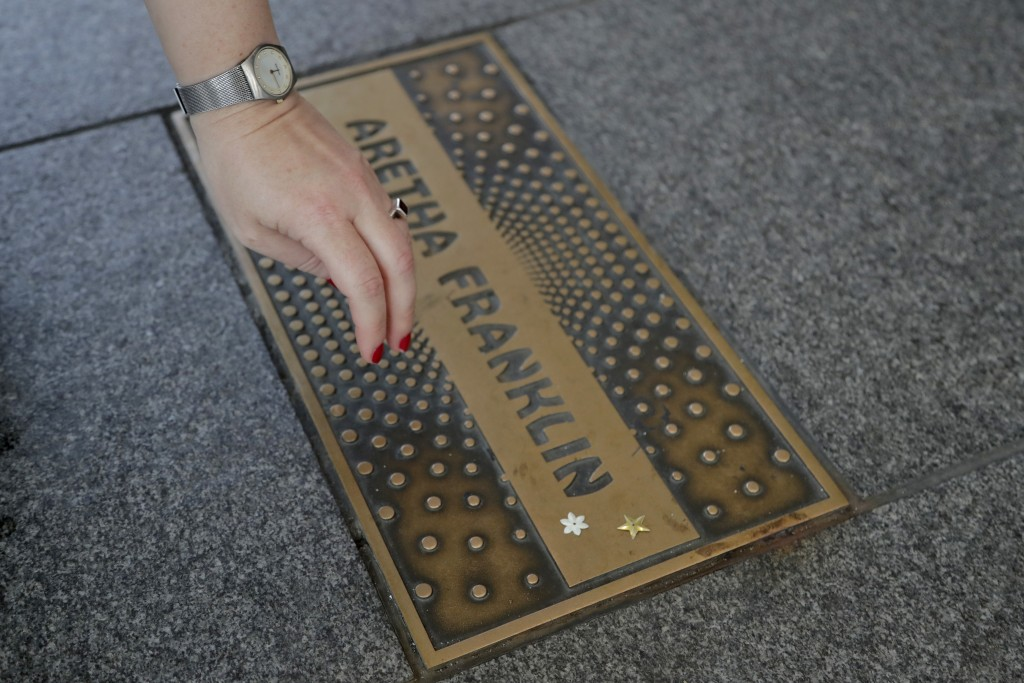 Agnieszka Mroczek, a tourist from Warsaw, Poland, pulls her hand away after placing stars on the nameplate for singer Aretha Franklin outside the Apol...