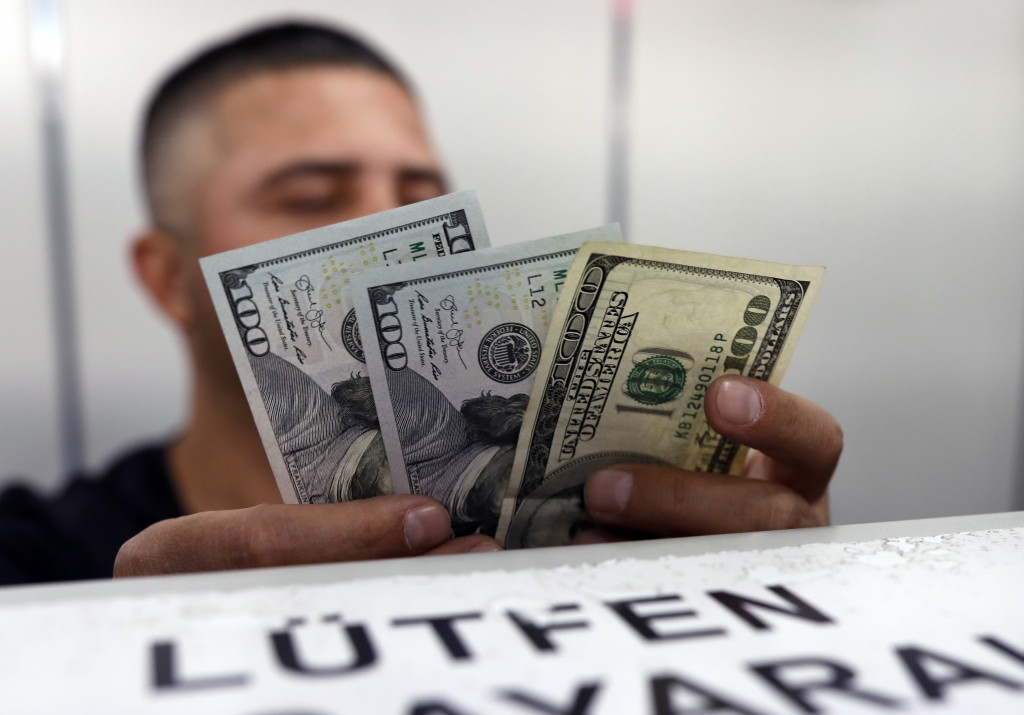An official checks US dollar banknotes before changing them for Turkish lira currency inside a currency exchange office in Ankara, Turkey, Friday, Aug...