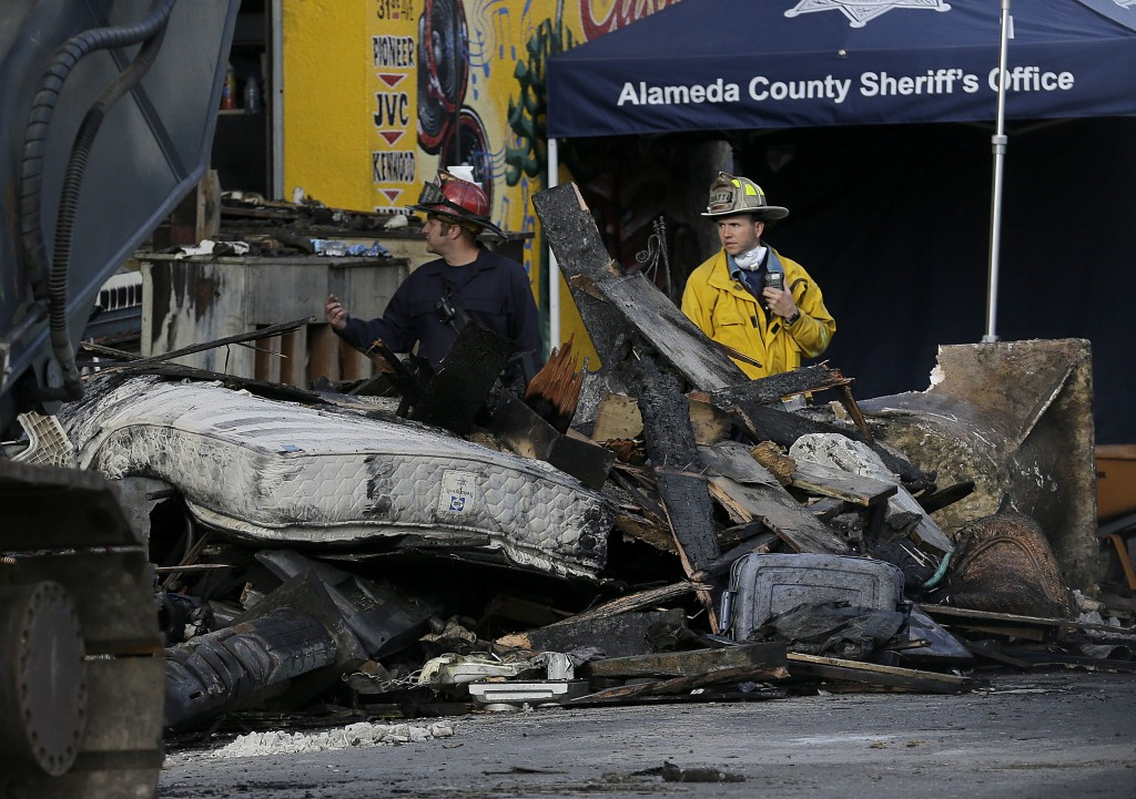 FILE - In this Dec. 6, 2016 file photo, crew workers walk behind debris from a warehouse fire in Oakland, Calif. A Northern California district attorn...