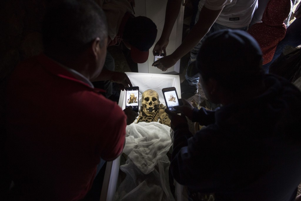 In this Aug. 14, 2018 photo, relatives take cell phone pictures of the remains of Fortunate Ventura Huamacusi, a man who was killed by the Peruvian ar...
