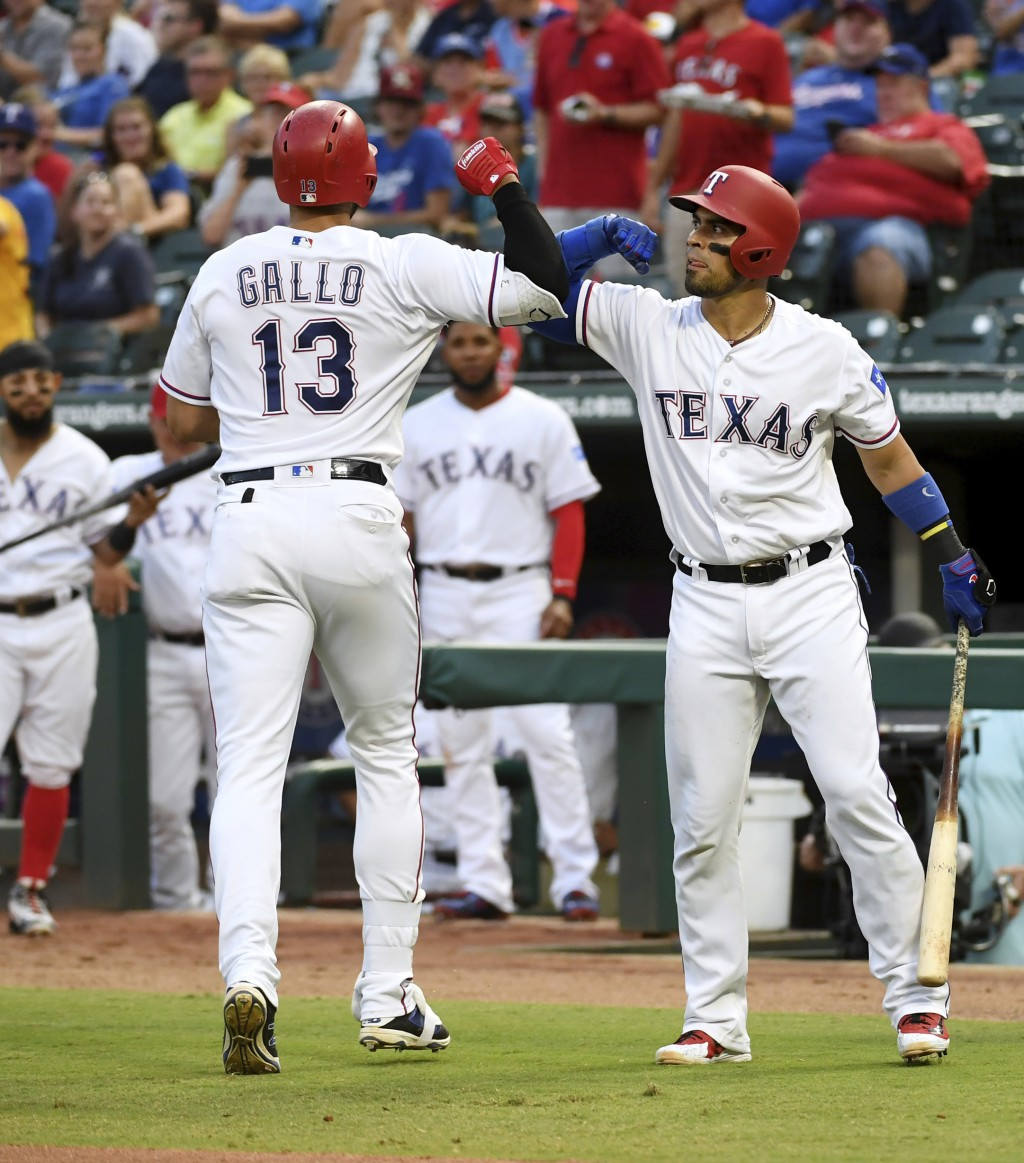 Texas Rangers' Joey Gallo (13) is congratulated by Robinson Chirinos, right, after hitting a solo home run off Los Angeles Angels starting pitcher Tay...