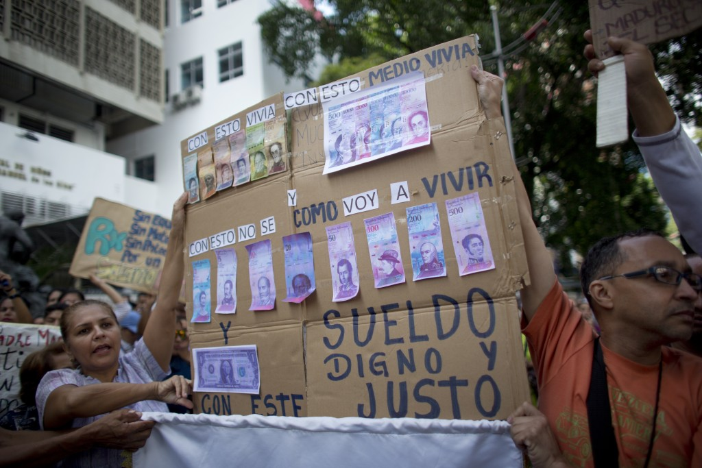 Nurses holds a sign with a fake Venezuelan's bills, representing how low their salaries have been devalued by inflation, during a protests against the...