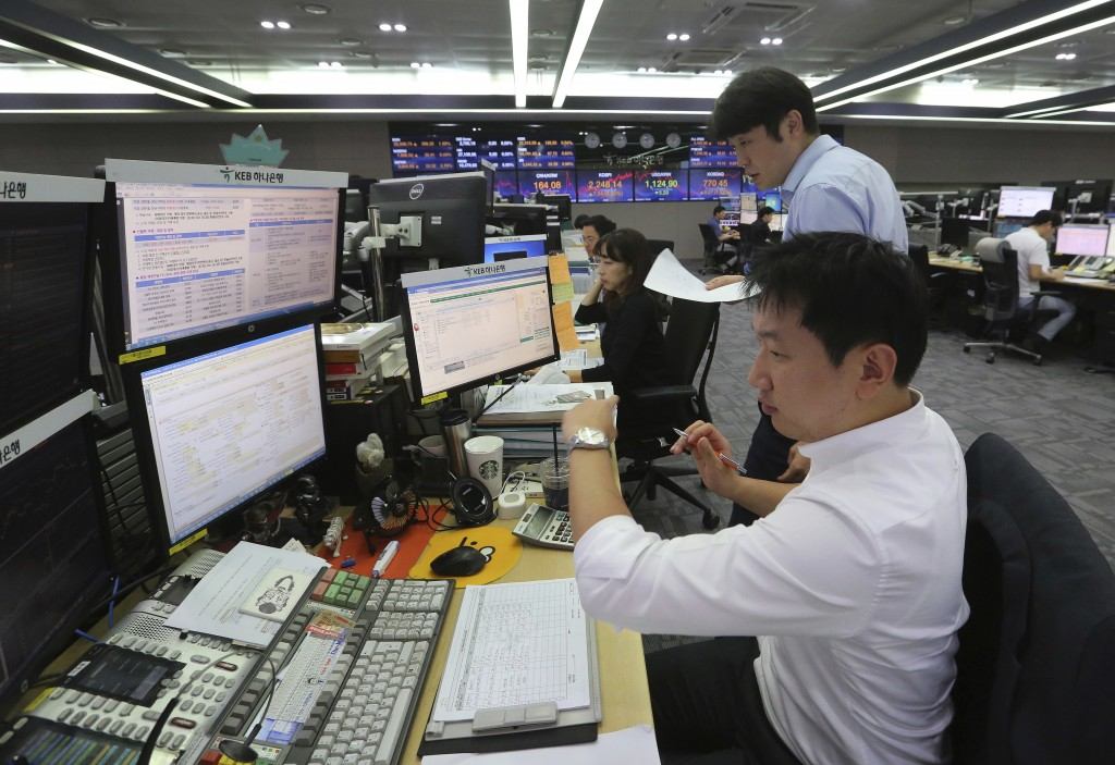 Currency traders work at the foreign exchange dealing room of the KEB Hana Bank headquarters in Seoul, South Korea, Friday, Aug. 17, 2018. Asian share...