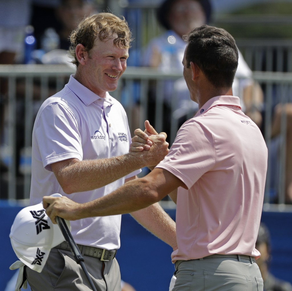 Brandt Snedeker, left, is congratulated by playing partner Billy Horschel, right, after finishing their round on the ninth hole during the first round...
