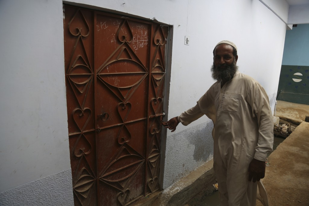 In this Aug. 6, 2018, photo, a man shows the locked house of suicide attacker Hafeez Nawaz, who killed 149 people and left dozens injured in Dhabeji, ...
