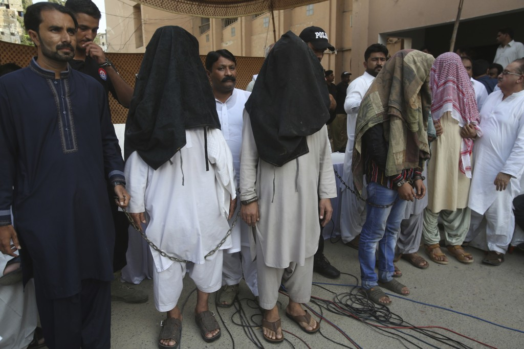 FILE - In this Aug. 10, 2018, file photo, family members of suicide bomber Hafeez Nawaz, with their faces covered, are presented before media for in K...