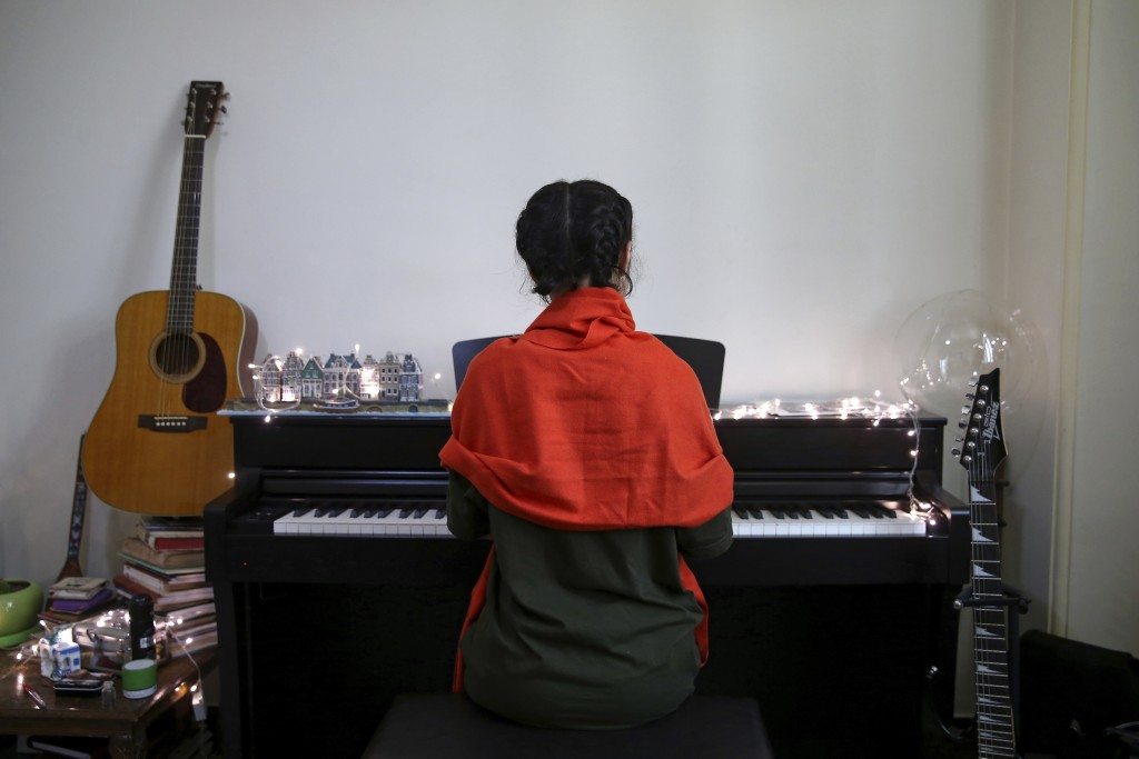 In this July 26, 2018 photo, Afghan musician Soraya Hosseini, a member of Arikayn rock band, plays piano in her house outside Tehran, Iran. The band m...