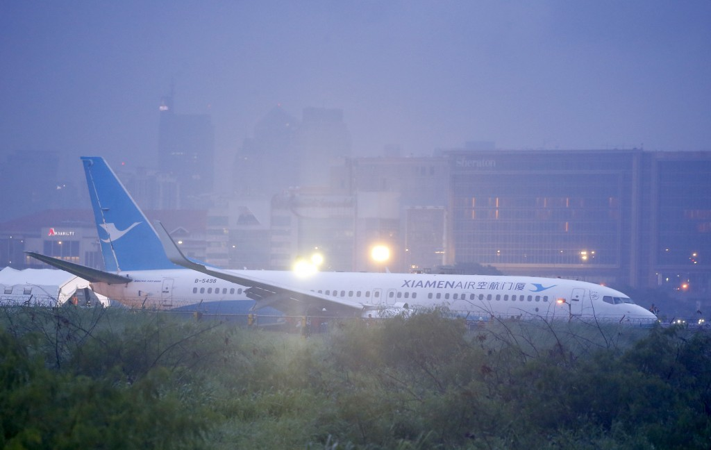 Rescuers are seen at the scene as a Boeing passenger plane from China, a Xiamen Air, lies on the grassy portion of the runway of the Ninoy Aquino Inte...