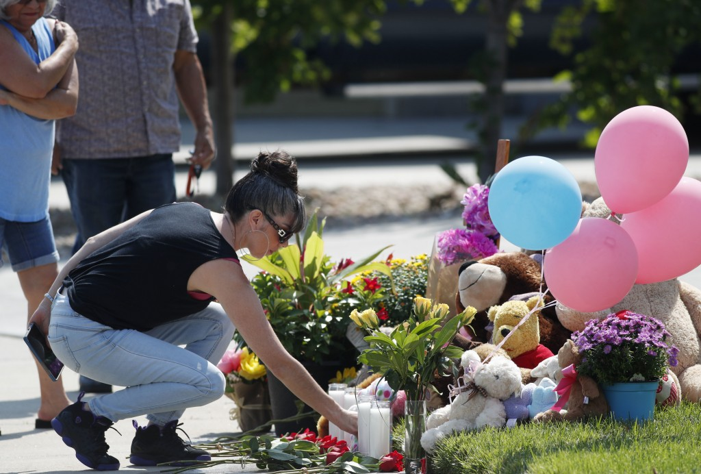 Irene Montoya of Aurora, Colo., places a bouquet of flowers as tributes grow outside the home where a pregnant woman and her two daughters lived Thurs...