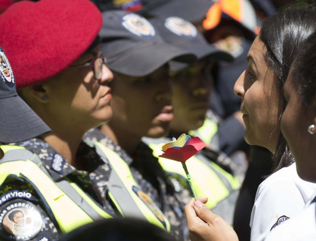 A nurse offers a paper flower to a police officer during a protest against the government of President Nicolas Maduro, in Caracas, Venezuela, Thursday...