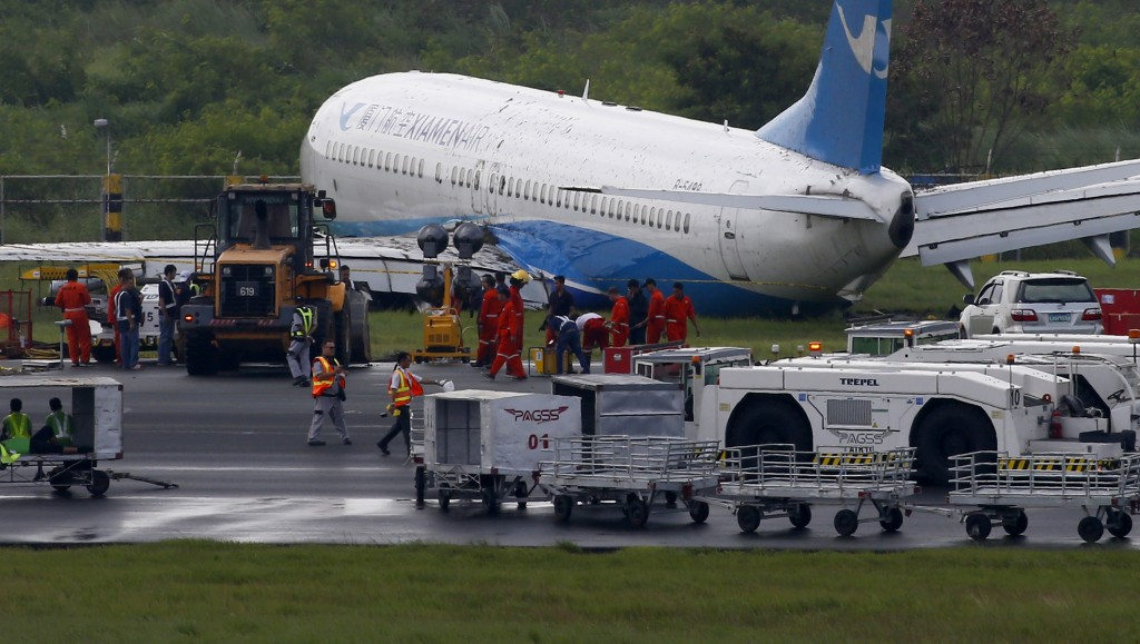Xiamen Air, a Boeing passenger plane from China, sits on the grassy portion of the runway of the Ninoy Aquino International Airport after it skidded o...