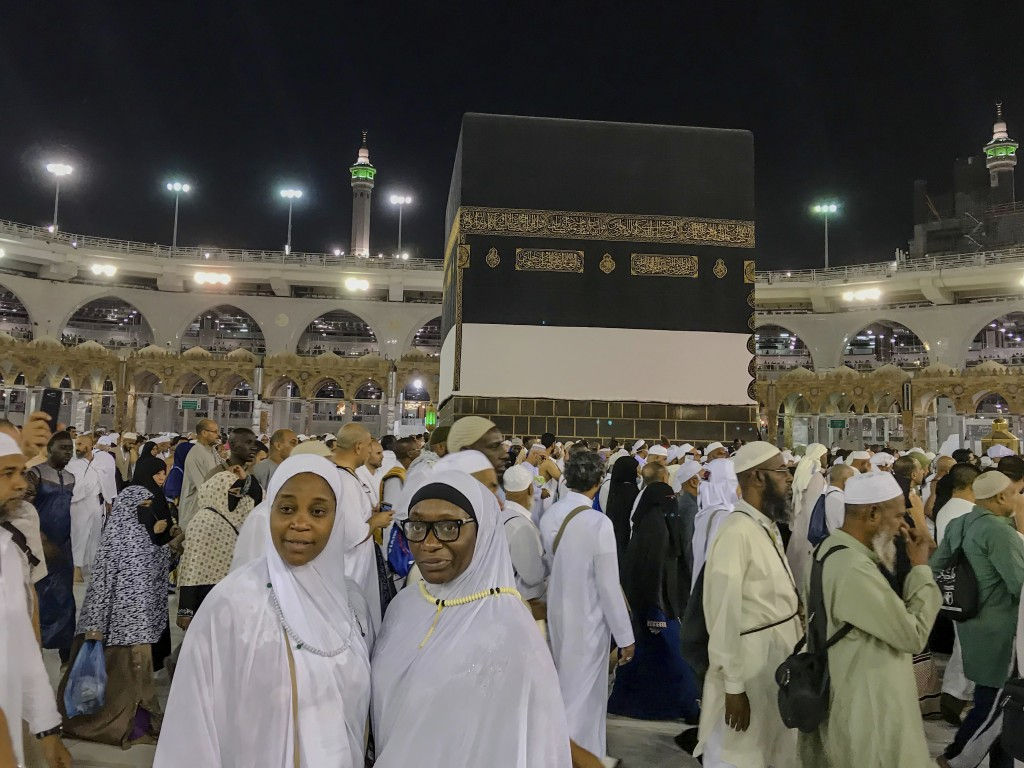 Muslim women pilgrims pose for photographs for their relative near the Kaaba, the cubic building at the Grand Mosque, in the Muslim holy city of Mecca...