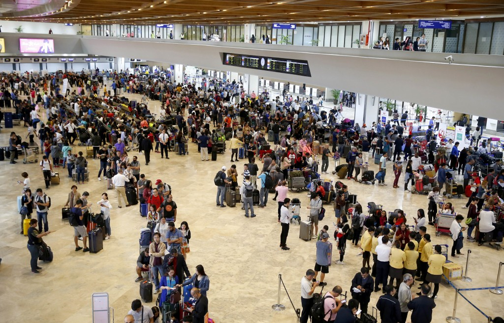 Hundreds of airline passengers gather to check their flights at the Ninoy Aquino International Airport after a Chinese Xiamen Air Boeing passenger pla...